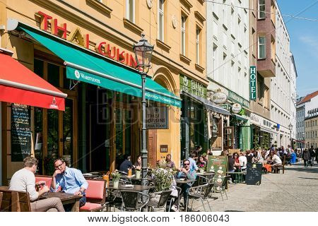 People Sitting In Restaurants And Cafes In The Streets Of Berlin Mitte On A Sunny Day.