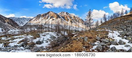 Nameless mountain peak and stream valley. Siberian alpine tundra in late April. Great Sayan. Munch-Sardyk. Russia