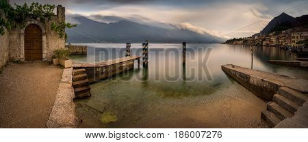 Old empty harbour in Limone sul Garda with cloudy mountains in background Italy