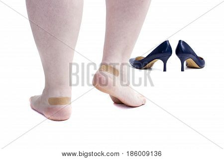 Female legs with plaster and shoes on white background