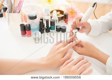 Salon Manicurist Using Electric Nail Drill