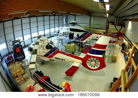 LONGYEARBYEN, SVALBARD, NORVAY - APRIL 23, 2013: AS-365N2 Dauphin 2 LN-OCO of Airlift AS in a hangar at Svalbard airport.