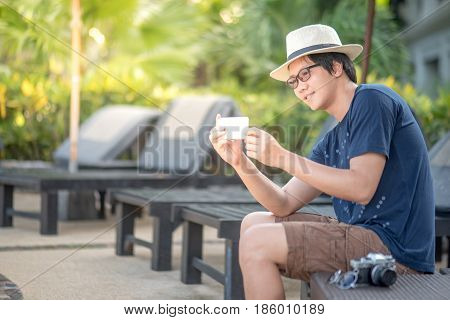 Young Asian happy man take photos in resort by smartphone for sharing on social media app using phone and digital age lifestyle concepts