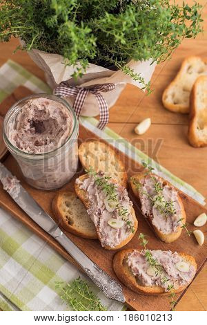 Bean pate with garlic and thyme on grilled crusty bread on wooden background.