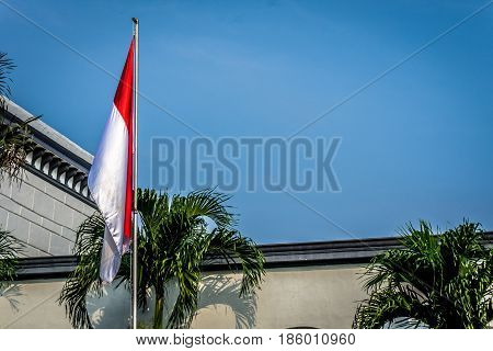 Indonesia flag on the mast with building as background photo taken in indonesia java