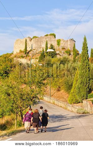 Elderly ladies walk home together at the foot of the Rocca Castle of Tentennano in Castiglione d'Orcia, Tuscany, Italy - 22 September 2011