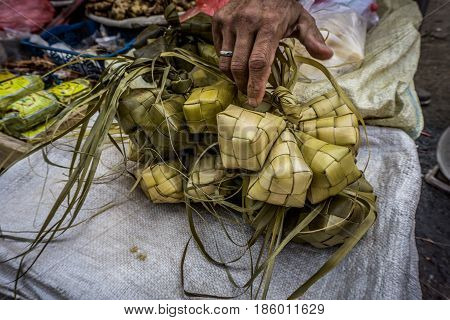 A hand touch rice wraped with coconut leaf with diamond shape in traditional market Bogor Indonesia java