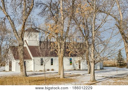 White country church with a new brown steel roof on a winter day