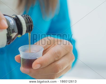 healthcare people and medicine concept - woman pouring medication or antipyretic syrup from bottle to cup