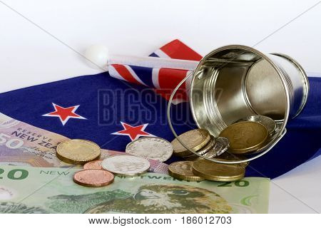 New Zealand dollars and coins spilt from a bucket and a NZ flag.
