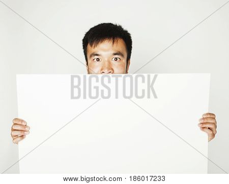 pretty cool asian man holding empty white plate smiling, making advert