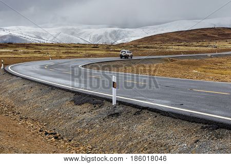 Car on the road Beautiful winter road in Tibet under snow mountain Sichuan China