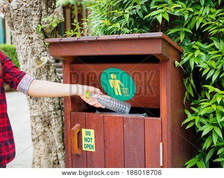 Closeup portrait hand throwing plastic empty water bottle in recycling bin trees background