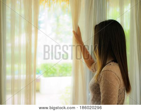 Rear view of a young woman holding the curtains open to look out of a large light window at home interior. Positive and aspirational lifestyle. Woman looking out a window indoors.