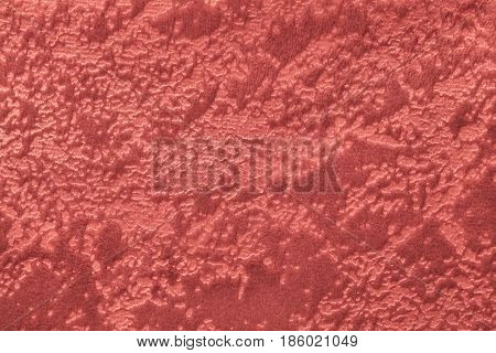 Dark red background from a soft upholstery textile material closeup. Coral spotted fabric with natural texture. Cloth backdrop.