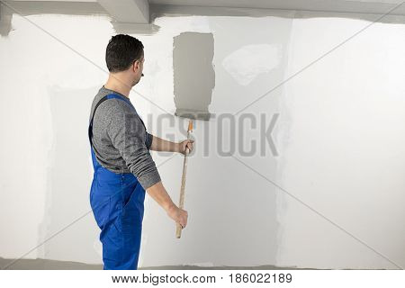 Manual worker wearing bib overalls painting the walls of a house.