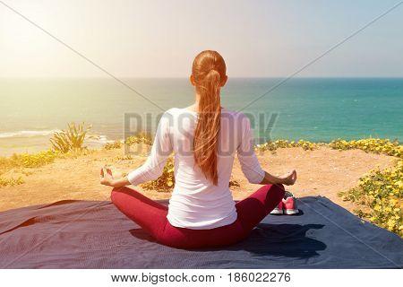 Young  Woman Yoga On The Sea Beach