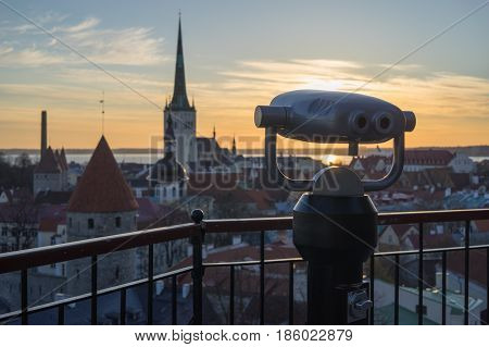 Coin-operated binoculars at viewing platform. Cityscape in sunrise on background