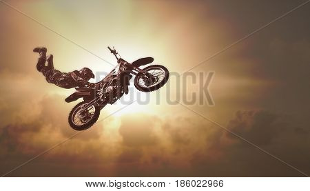 Extreme sports background - silhouette of biker jumping on motorbike on sunset stunt