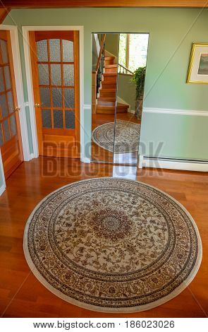 Wooden french doors and area rug at the house entrance. Interior design of luxury residential house