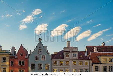 Colorful medieval houses against wonderful morning sky and clouds. Cozy european old town street