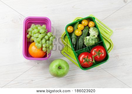 Lunch box with vegetable and fruits on wooden table. Kids take away food box. Top view