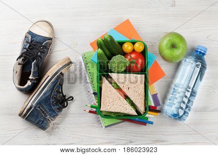 Lunch box with vegetables and sandwich on wooden table. Kids take away food box and sneakers. Top view