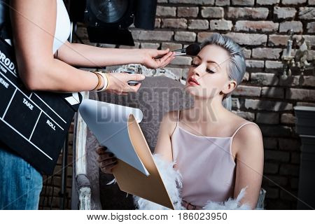 Makeup artist working on young diva before filming.