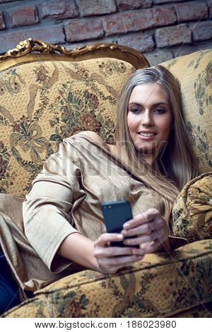 Young woman resting on sofa at home, using mobilephone, texting.