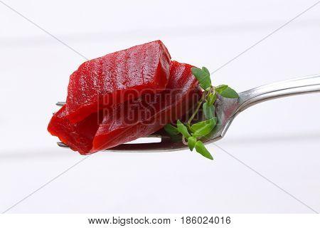 sliced and pickled beetroot on fork