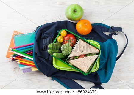 Lunch box with vegetables and sandwich on wooden table. Kids take away food box and school backpack. Top view