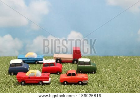 Miniature toy cars on green grass over blue sky and clouds. Traffic congestion.