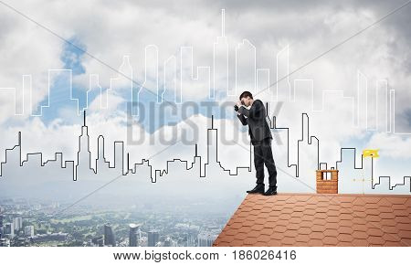 Young businessman viewing cityscape in his binoculars Mixed media