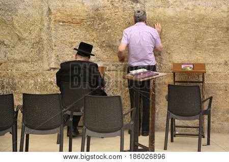 JERUSALEM, ISRAEL - APRIL 30, 2017: Religious Jews pray by the Western Wall inside of the Western Wall Tunnel at the Old City of Jerusalem.