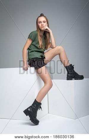 Young slender model sitting on white cube. girl dressed in green T-shirt, black shorts and large army boots