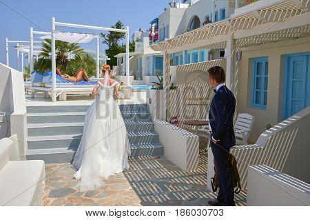 SANTORINI, GREECE - AUGUST 05, 2015: Young bride in white dress and bridegroom on Santorini