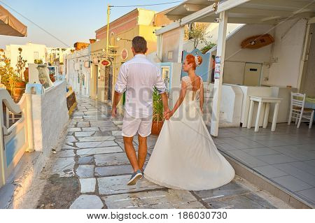 SANTORINI, GREECE - AUGUST 06, 2015: young couple walking in the morning on Santorini island