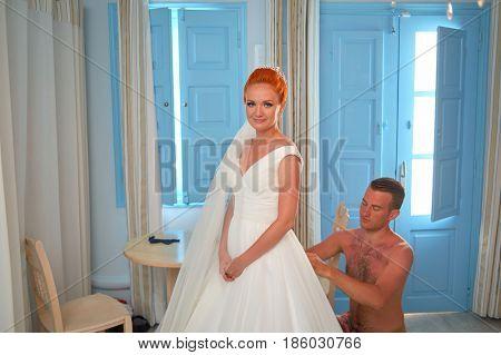 SANTORINI, GREECE - AUGUST 05, 2015: Man tighten wedding dress on beautiful young bride
