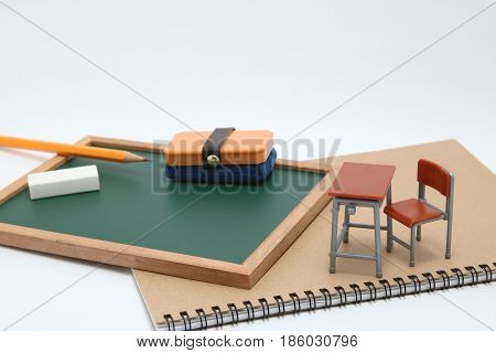 Miniature school desk, chalkboard and notebook on white background. Education concept.