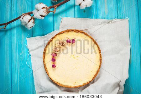 Homemade cheesecake - healthy organic summer dessert pie cheesecake. Cheese cake on blue wood table. Decoration of dried flowers. Top view