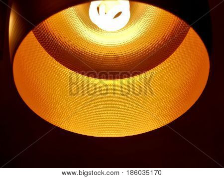 Closed up of black orange ceiling lamp with energy saving fluorescent light bulb