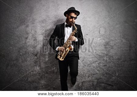 Jazz musician playing a saxophone and leaning against a rusty gray wall