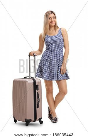 Full length portrait of an attractive young woman in a dress with a suitcase isolated on white background