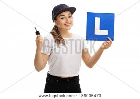 Happy teenage girl holding a car key and an L-sign isolated on white background
