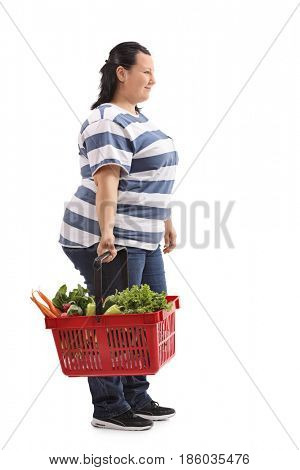 Full length profile shot of an overweight woman holding a shopping basket filled with vegetables and waiting in line isolated on white background