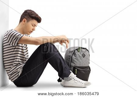 Sad teenage student sitting on the floor and leaning against a wall isolated on white background