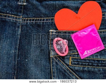 Save sex concept. Pink condom in blue jeans pocket and Aids awareness red ribbon