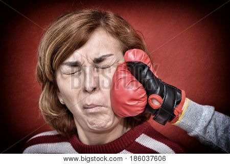 Woman being punched with red boxing glove in her face. Computer added dust, scratches, grain and vignette.