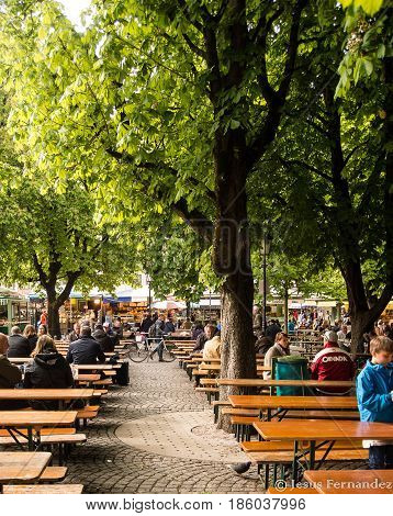 Munich,Germany-May 9,2017:Tourists and locals talk and drink beer at a beergarden near Marienplatz