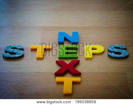 next steps concept in colorful letters on wooden blackboard